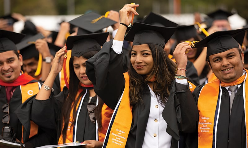 cal state fullerton graduates getting ready to throw their caps