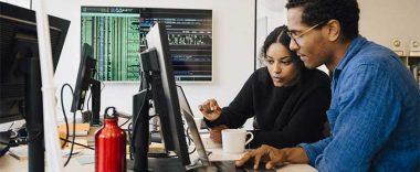 Decorative stock image of individuals looking at a computer screen