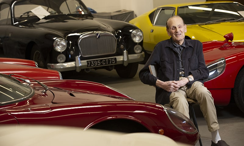 Nick Begovich poses with his extensive collection of sports and grand touring cars.